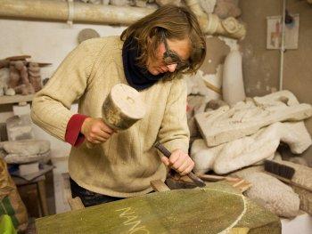 Eine Frau arbeitet in der Steinmetzwerkstatt