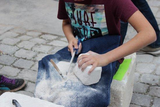 Junge bearbeitet einen Stein mit Werkzeug