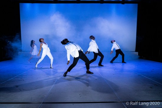 Lukas Kientzler, Challenge Gumbodete, Bobby Briscoe, Anne-Sophie Azizè Flittner und Samira Vinciguerra stehen seitlich zum Publikum. Ihr Oberkörper und Köpfe sind nach hinten in Richtung Boden gewandt. Sie tanzen. Der Raum wird blau angeleucht.
