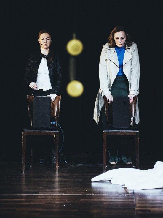 Zwei Frauen stehen jeweils hinter der Lehne eines leeren Stuhles und schauen nachdenklich auf den Boden