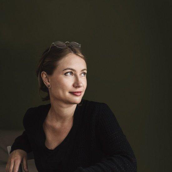 Portrait von Rebecca Trescher. Sie hat ihre Haare zu einem Zopf zusammengebunden, hat ihre Sonnenbrille auf dem Kopf und trägt einen schwarzen Pullover. Ihr Blick ist zur Seite gerichtet.