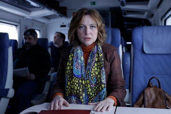 Eine Frau sitzt an einem Tisch in einem Zugabteil und schaut direkt in die Kamera.