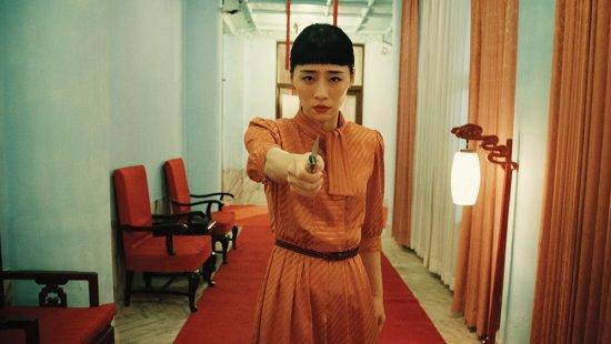 Eine Frau steht in einem Flur und hält mit ausgestrecktem Arm ein Messer in die Kamera.