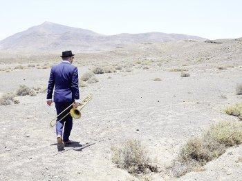 Samuel Blaser spazier mit seiner Posaune in der Hand in der Wüste von Lanzarote