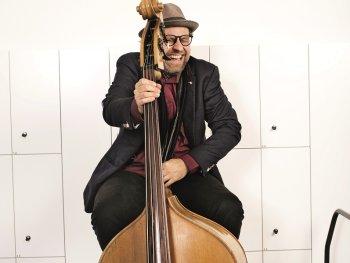 Georg Breinschmid sitzt breit grinsend auf einem Hocker. Er hält in der rechten Hand ein Cello.