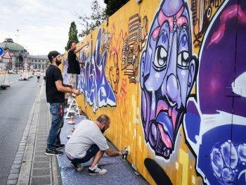 Graffiti-Künstler bei ihrer Arbeit am Bauzaun des Künstlerhauses