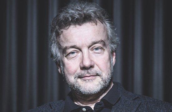 Portrait von Johannes Rumstadt. Er lächelt und schaut in die Kamera. Der Hintergund ist grau.