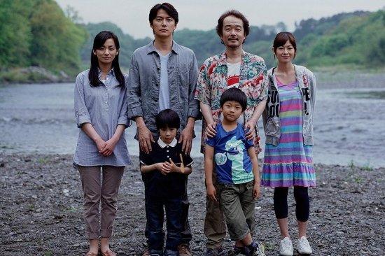 Filmplakat zu LIKE FATHER, LIKE SON. Eine Familie mit zwei Kindern, zwei Frauen und zwei Männern stehen an einem Fluss.