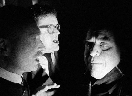 Drei Männer haben die Köpfe eng zueinandergewandt und sprechen miteinander. Das Bild ist schwarzweiß.