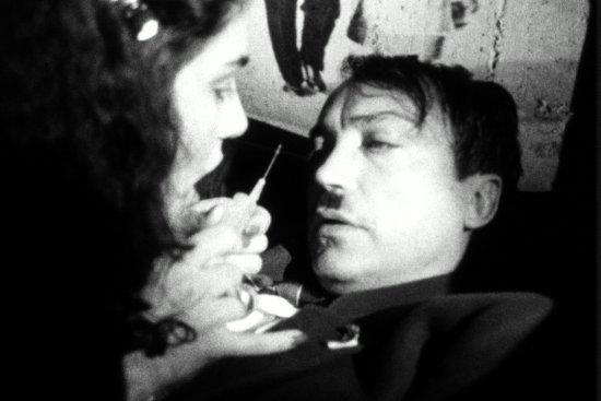 Eine Frau hält einem Mann eine Spritze unter die Nase. Das Bild ist schwarzweiß.