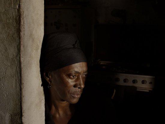 Eine Frau, zu sehen im Profil, steht angelehnt an einem Türpfosten.