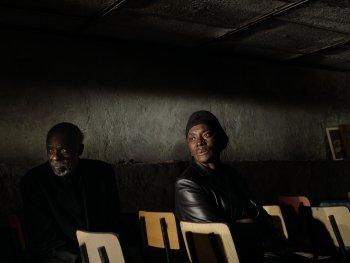 Eine Frau und ein Mann sitzen auf Stühlen in einem dunklen Raum und schauen nach links.
