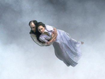 Ein Mann hat eine Frau im Arm und schwebt im grauen Himmel über eine Stadt