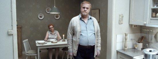 Eine Frau sitzt im HIntergrund an einem Küchentisch. Vor ihr steht ein Mann mit Blick in die Kamera.
