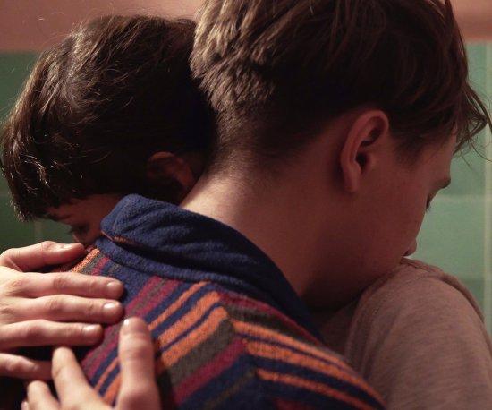 Eine junge Frau und ein junger Mann umarmen sich.
