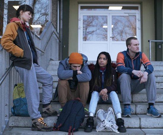 Vier Jugendliche sitzen auf einer Treppe vor einem Gebäude und warten.