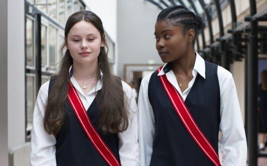 Zwei Mädchen in Schulinform laufen nebeneinnander einen Flur entlang.