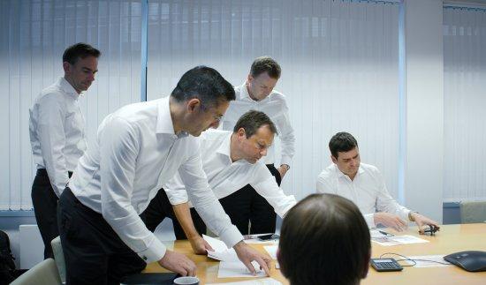 Geschäftsmänner stehen und sitzen verteilt an einem Tisch in einem Konferenzraum.