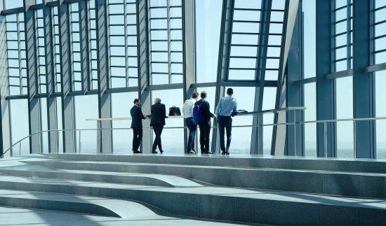 Geschäftsmänner stehen an der Glasfront eines Bürogebäudes und schauen hinaus.