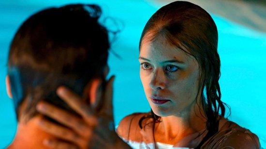 Eine Frau und ein Mann sind im Swimmingpool. Die Frau hält den Kopf des Mannes in ihren Händen.