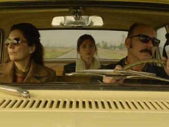 Eine Familie mit Vater, Mutter und Kind fahren in einem Auto.