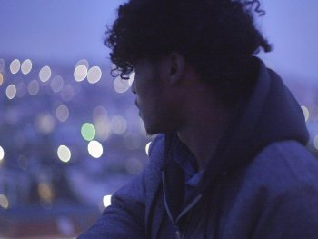 Ein Mann schaut auf die Lichter einer Stadt.