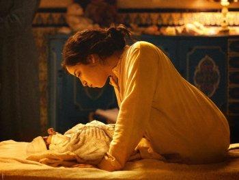 FIlmplakat zu ADAM. Eine Frau sieht ein Baby an, welches auf dem Bett liegt.