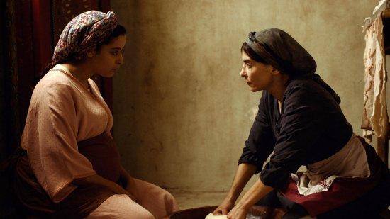 Zwei Frauen sitzen sich am Boden gegenüber und schauen sich an.