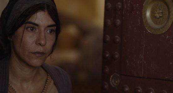 Eine Frau mit Kopftuch sieht aus eine Tür heraus.