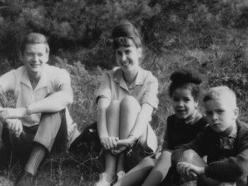 Schwarzweiß Foto einer vierköpfigen Familie, die auf einer Wiese sitzt.