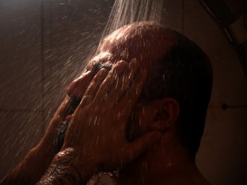 Ein Mann steht unter der Dusche und reibt sich mit den Händen im Gesicht.