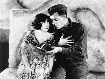 Schwarzweiß-Foto. Ein Soldat liest einer Frau aus einem Buch vor.