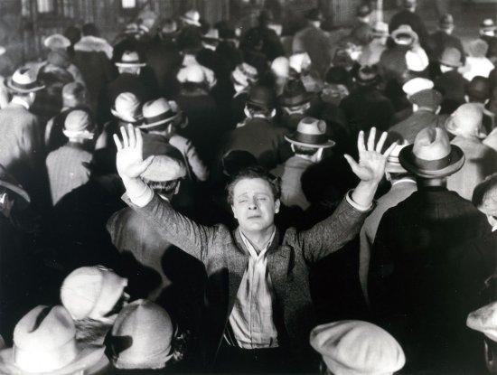 Schwarzweiß-Foto. Ein Mann steht in einer Menschenmasse und streckt seine Arme nach oben.