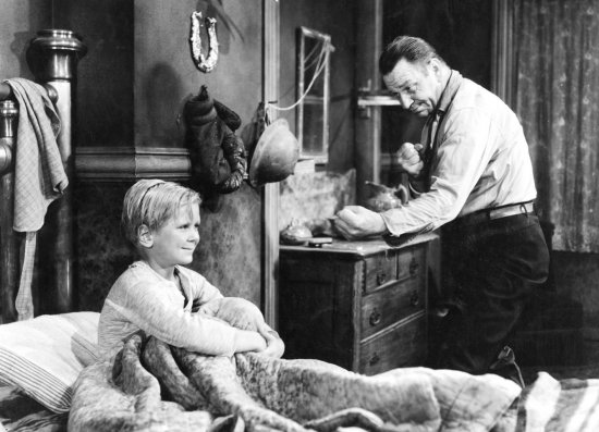 Schwarzweiß-Foto. Ein Junge sitzt in einem Bett. Ein Mann daneben spielt Schattenboxen mit ihm.