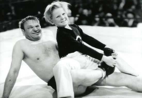 Schwarzweiß-Foto. Ein Junge sitzt mit einem Boxer am Boden eines Boxringes.