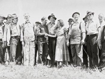 Schwarzweiß-Foto. In der Mitte einer Menschenmenge geben sich eine Frau und ein Mann die Hand.