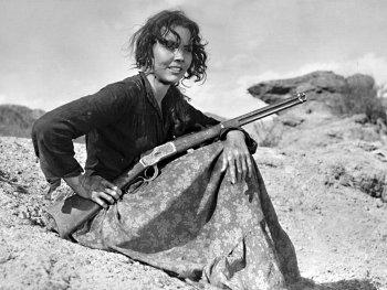 Schwarzweiß-Foto. Eine Frau sitzt mit einem Gewehr in der Hand auf einem Hügel.
