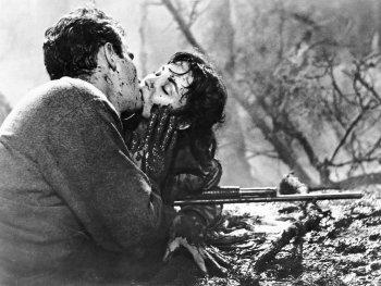 Schwarzweiß-Foto. Eine Frau und ein Mann knien im Schlamm und küssen sich.