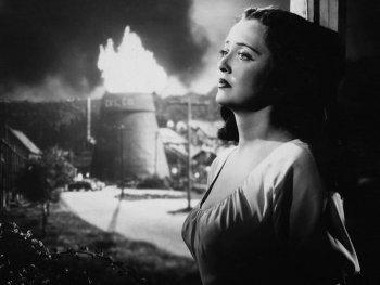 Schwarzweiß-Foto. Eine Frau lehnt an einem Fensterrahmen. Hinter brennt ein Turm.