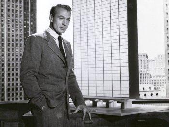 Schwarzweiß-Foto. Ein Mann steht an einem Schreibtisch.