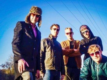 die 4 Mitglieder der Killing Popes und Oliver Steidel, draußen, blauer Himmel im Hintergrund