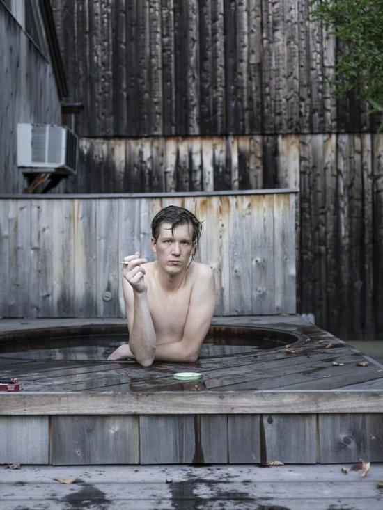 Junger Mann lehnt am Beckenrand eines Außenwhirlpools mit Holzverkleidung, raucht eine Zigarette und blickt in die Kamera.