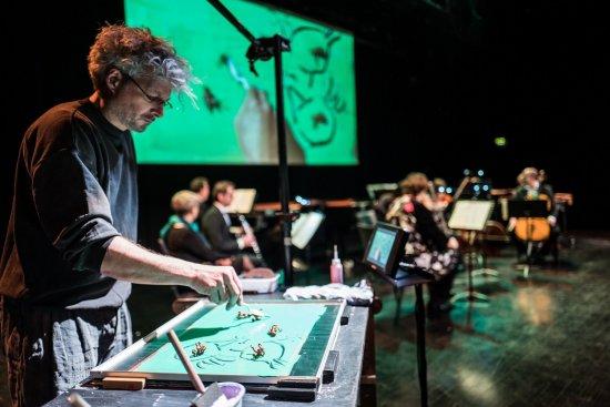 Joachim Torbahn bewegt Figuren auf seinem Bild. Dies wird im Hintergrund auf eine Leinwand gestreamt. Vor der Leinwand sitzt das Orchesta und begleitet alles musikalisch.