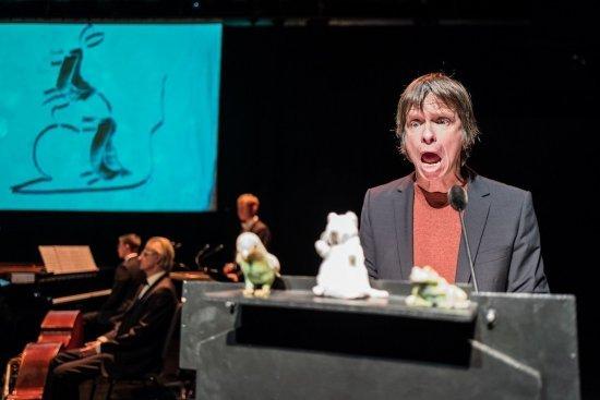 Tristan Vogt steht vor einem Rednerpult. Auf diesem befinden sich drei kleine Tierfiguren. Er hat einen erschrockenen Gesichtsausdruck mit weit offenem Mund. Im Hintergrund sieht man das Orchesta und die eine Leinwand, auf der eine Zeichnung von einem Tier zu sehen ist.