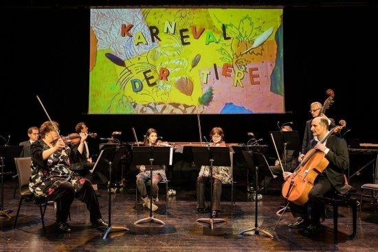 """Das ensemble KONSTRASTE-Orchesta sitzt auf der Bühne mit seinen jeweiligen Instrumenten. Alle haben vor sich ein Notenpult, worauf sie schauen. Im Hintegrund sieht man eine Leinwand, auf der buntes Papier mit der Aufschrift """"Karneval der Tiere"""" zu sehen ist."""