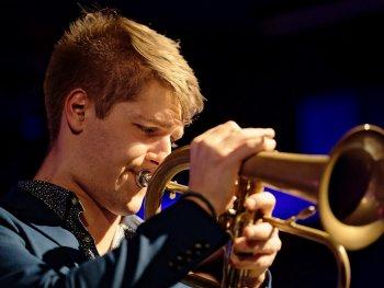 Das Sunday Night Orchestra steht mit seinen Instrumenten vor der Tafelhalle und lächelt in die Kamera