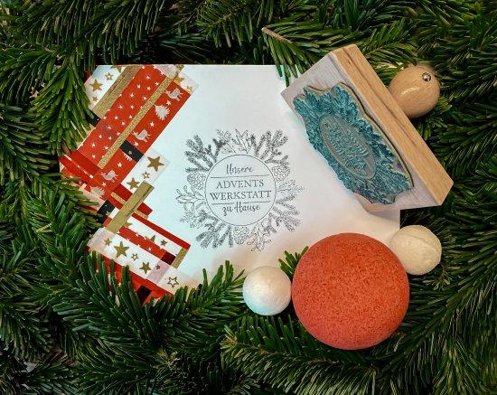 Auf einer weißen Postkarte umrahmt von Tannengrün sieht man einen Stempel, Badekugeln, weihnachtlich verziertes Tape-Band