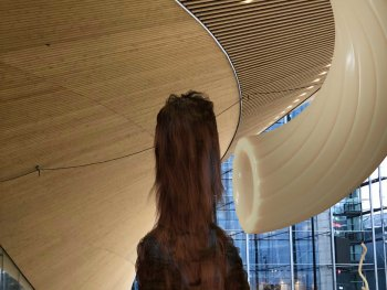 große Tierfigur steht vor einem Glasgebäude. Oben rechts aus der Ecke ist eine Pasta auf dieses gerichtet. Im Hintergrund gibt es zudem kleine Nudelfiguren.