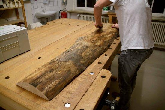 Mann bearbeitet eine Baumscheibe