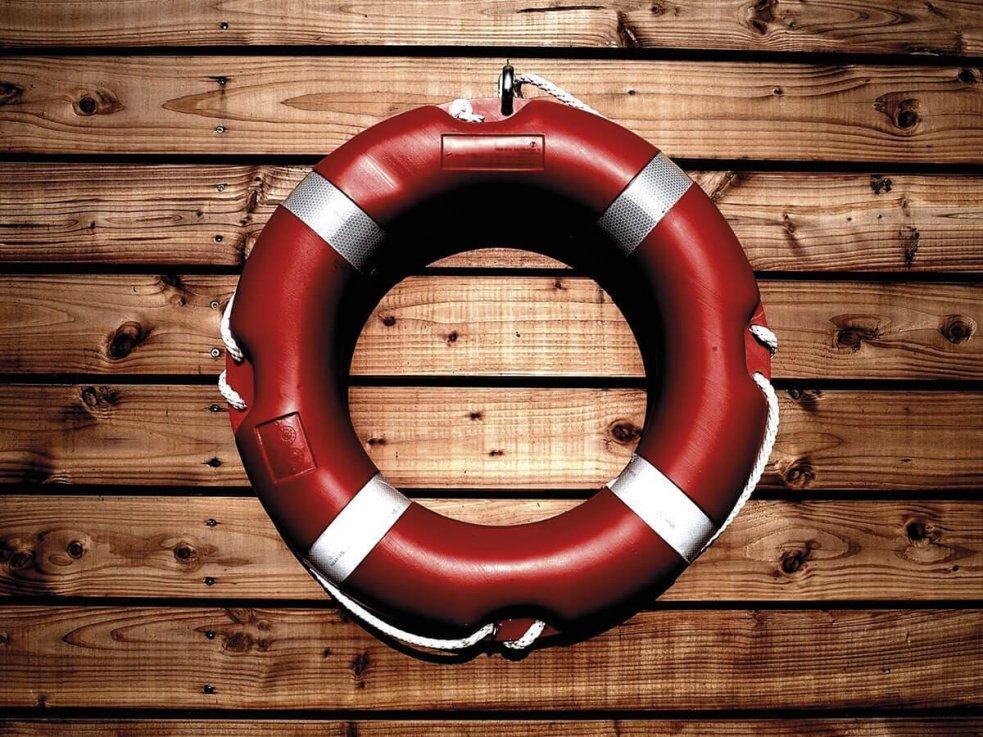 Rettungsring hängt vor einer Holzwand